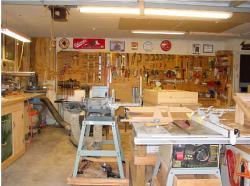 2. A view from the door of the garage which shows the Delta Sanding Center; table saw and rear wall of garage where tools are stored for easy use. Note the large out feed table for the table saw. It is actually the full length of the table saw and fence table; 4' X 8'. You also get a very good view of the tube sander attachment on the sanding station. It is a very good tool for shaping parts after being cut on the band saw.